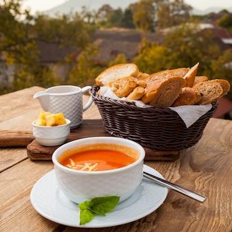 Heerlijke soepmaaltijd in een kom met mening van de brood de hoge hoek met een bos op achtergrond