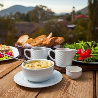 Heerlijke soepmaaltijd met brood, greens, salade in een kom met dorp op achtergrond, hoge hoekmening.