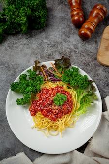 Heerlijke spaghetti geserveerd met mooie ingrediënten.