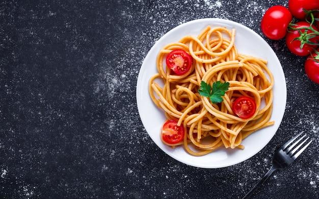 Heerlijke spaghetti met peterselie, tomatenkers en tomatensaus op een plaat. italiaans eten en pasta. bovenaanzicht