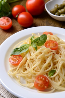 Heerlijke spaghetti met tomaten op plaat op tafel close-up