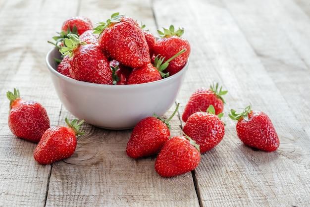 Heerlijke stawberries in een kom op houten tafel met groene bokeh achtergrond, zomerfruit en vitaminen