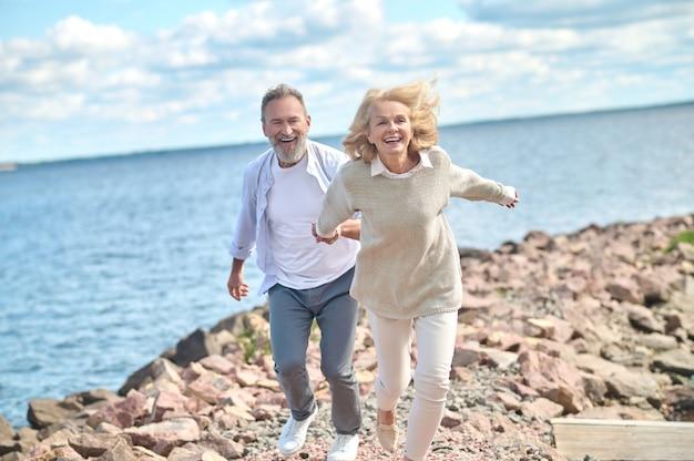 Heerlijke stemming. enthousiaste lachende vrouw met wind in haar haar die de hand van een bebaarde man vasthoudt die op mooie dag langs de kust rent
