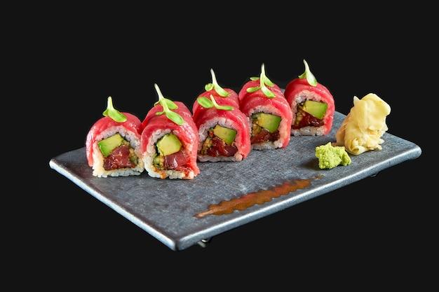 Heerlijke sushirol met tonijn, avocado en komkommer, geserveerd op een keramisch bord met gember en wasabi. geïsoleerd op een zwarte achtergrond. japans eten