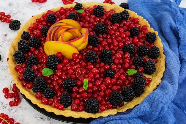 Heerlijke taart met rode bessen, perzik en bramen