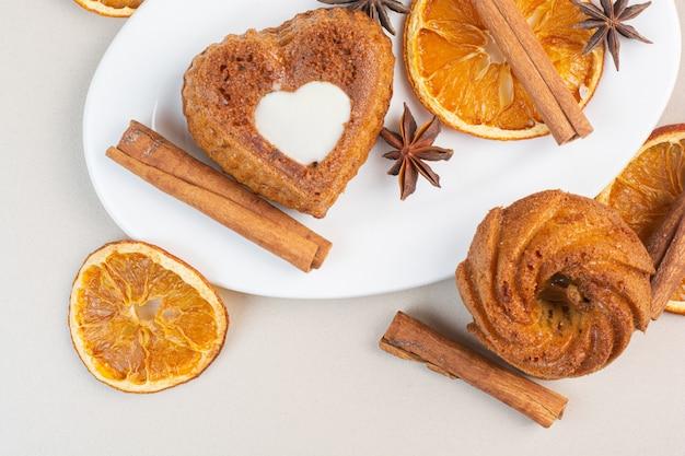 Heerlijke taarten, gedroogde citroen, anijs en kaneelstokjes op een bord, op het marmer.