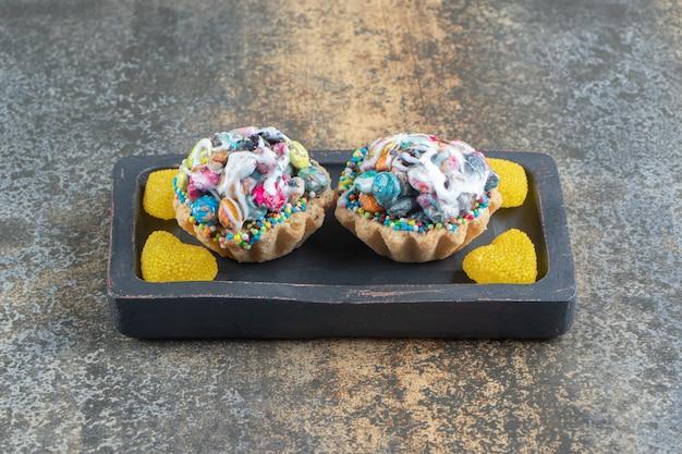Heerlijke taarten met snoepjes in de vorm van een hart op een donkere houten bord