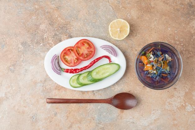 Heerlijke thee met komkommer, tomaat, schijfje citroen en lepel op witte plaat