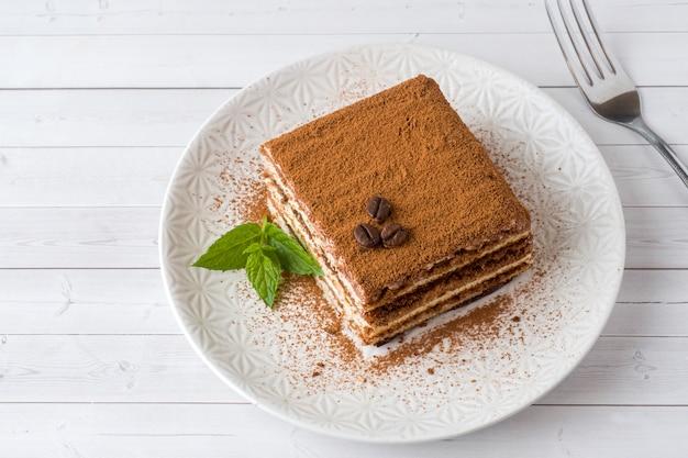 Heerlijke tiramisu-cake met koffiebonen en verse munt op een pl