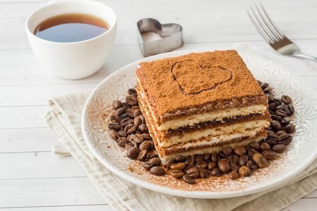 Heerlijke tiramisu-cake met koffiebonen op een plaat en een kop