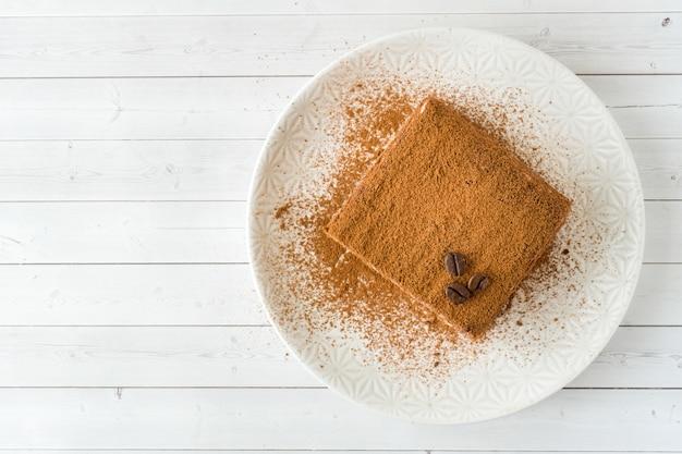 Heerlijke tiramisu-cake met koffiebonen op een plaat op een licht