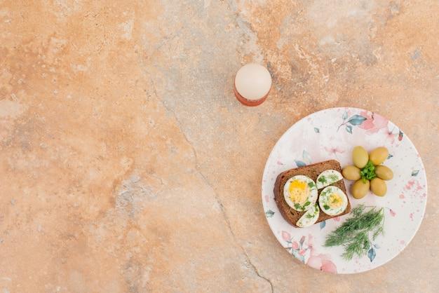 Heerlijke toast met gekookte eieren en olijven op de plaat