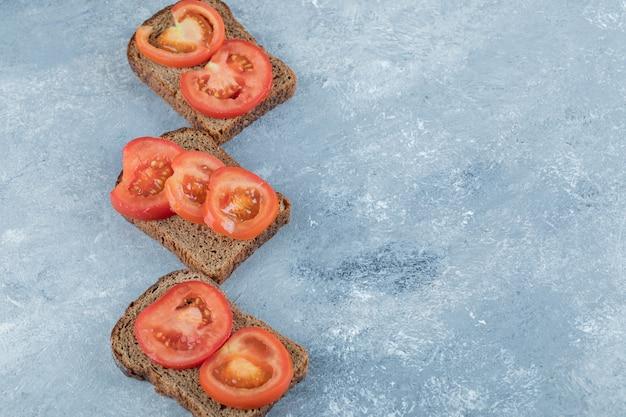 Heerlijke toast met plakjes tomaat op een grijze achtergrond.