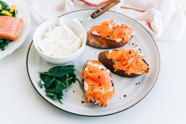 Heerlijke toast met zalm en kaasroom op een witte plaatwhit spinazie.