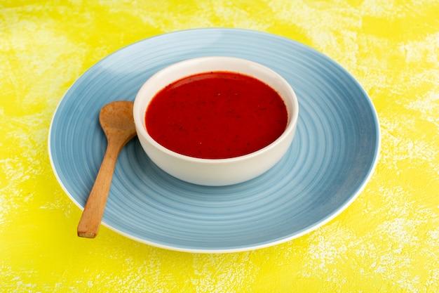Heerlijke tomatensoep binnen blauw bord op geel, soepmaaltijd diner plantaardig voedsel