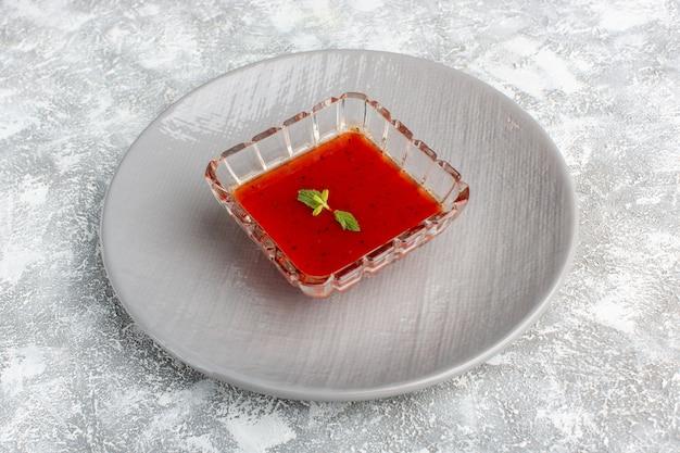 Heerlijke tomatensoep in grijze plaat op grijs, soepmaaltijd diner plantaardig voedsel