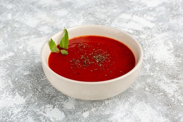Heerlijke tomatensoep in witte plaat op grijs-wit, soep maaltijd diner plantaardig voedsel