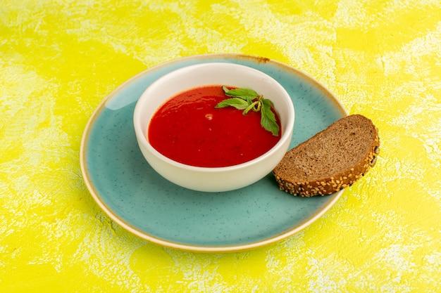 Heerlijke tomatensoep met broodbrood op het gele, plantaardige voedsel van de soepmaaltijd