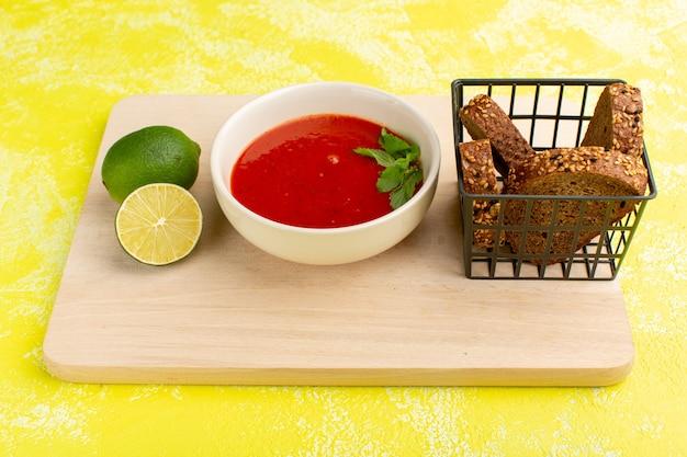 Heerlijke tomatensoep met broodbroodjes en citroenplak op geel, het dinergroente van de soepmaaltijd