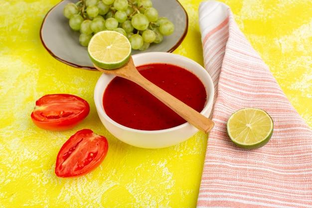 Heerlijke tomatensoep met citroen en groene druiven op geel, het plantaardige voedsel van het soepmaaltijddiner