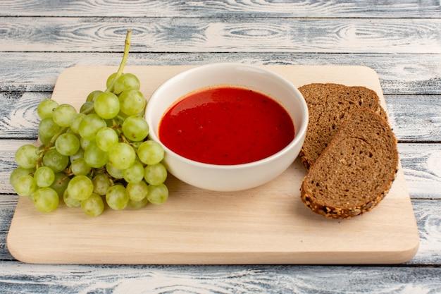 Heerlijke tomatensoep met donkere broodbroodjes en groene druiven op grijs, het diner van de soepmaaltijd