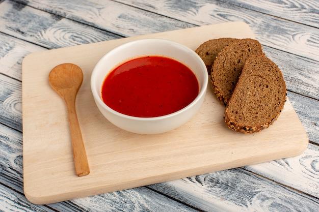 Heerlijke tomatensoep met donkere broodbroodjes op het grijze, soepmaaltijddiner