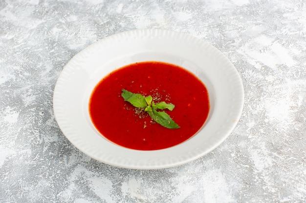 Heerlijke tomatensoep met kruiderijen op grijs, soep maaltijd diner groente