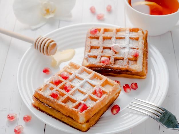 Heerlijke verrukkelijke weense wafels met honing en granaatappelzaden op een witte plaat
