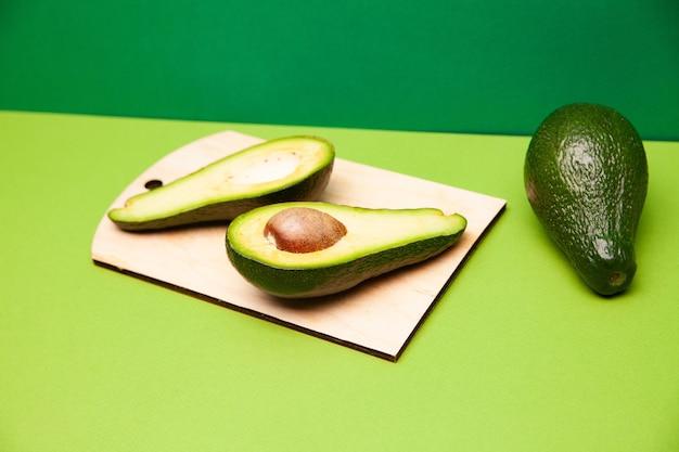Heerlijke verse avocadovruchten gerangschikt op groen oppervlak