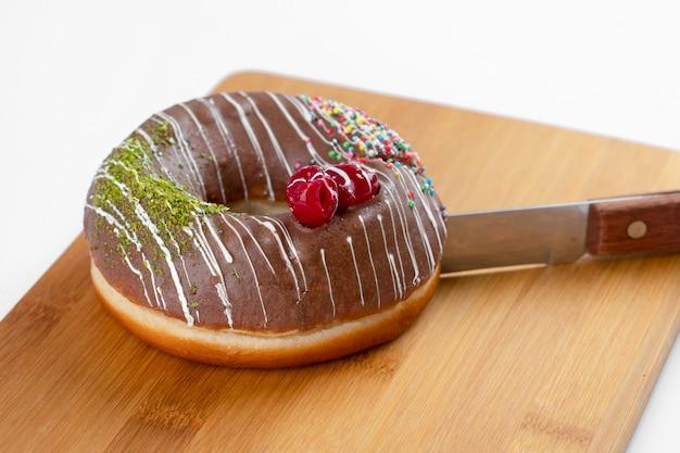 Heerlijke verse chocolade donuts liggend op een houten achtergrond.