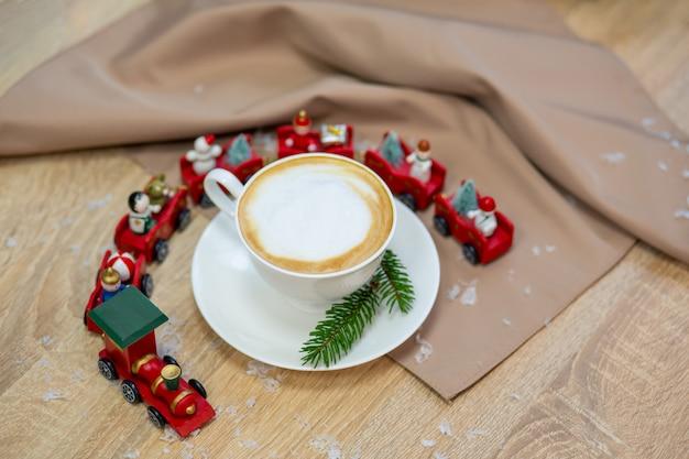 Heerlijke verse feestelijke ochtendcappuccinokoffie in een keramische witte kop op de houten tafel met decoratieve kersttrein, rode sierplanten, vuurvliegjes en vuren takken.