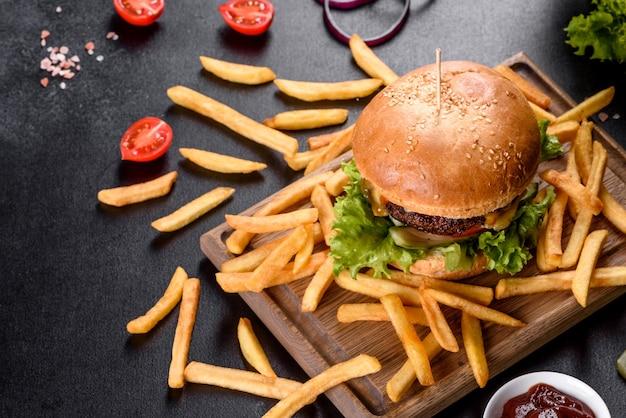 Heerlijke verse hamburger met runderkotelet, tomaten en sla met frietjes. ongezonde voeding