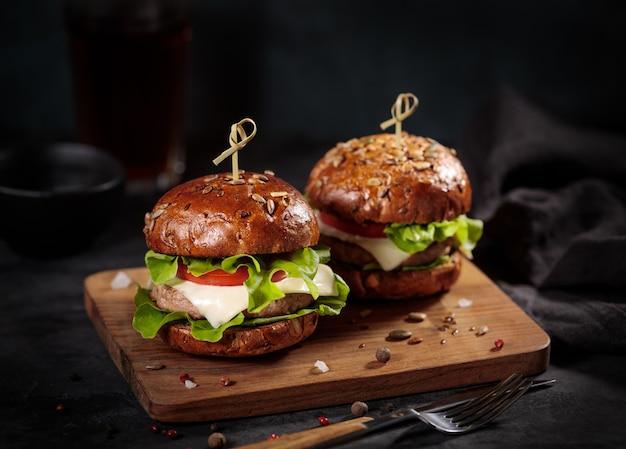 Heerlijke verse hamburgers met kaas op graanbroodjes geserveerd op een houten bord