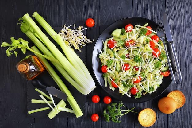 Heerlijke verse pastasalade met plakjes komkommer, stengels bleekselderij, tomaat en taugé op zwarte plaat op zwarte houten tafel met sesamolie en ingrediënten op de achtergrond