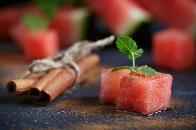 Heerlijke verse plakjes watermeloen met kaneel op de donkere achtergrond.