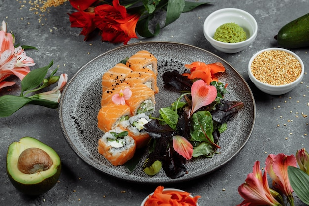 Heerlijke verse sushibroodjes met zalm en de kaas van philadelphia op grijze plaat