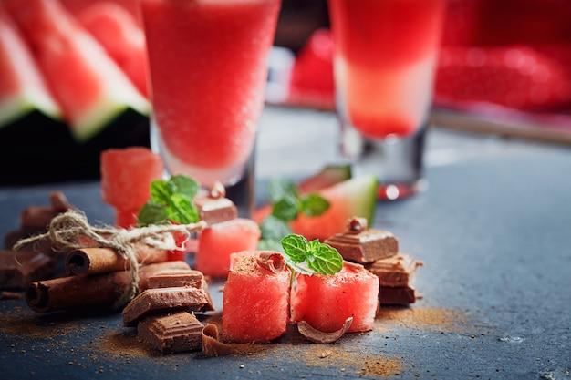 Heerlijke verse watermeloencocktail, stukjes chocolade en kaneel op de donkere achtergrond.