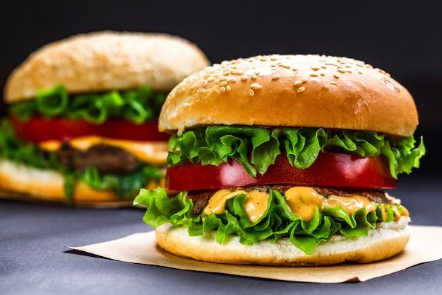 Heerlijke verse zelfgemaakte hamburgers op een donkere. snel en slecht eten