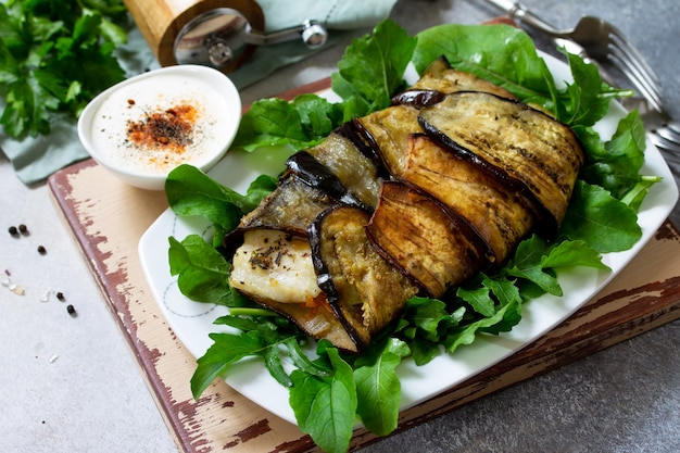 Heerlijke vis gebakken met groenten in een aubergine gegrild op een stenen of leistenen tafel