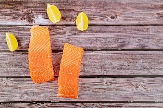 Heerlijke vis rauwe zalmfilet met plakjes citroen op een houten bord