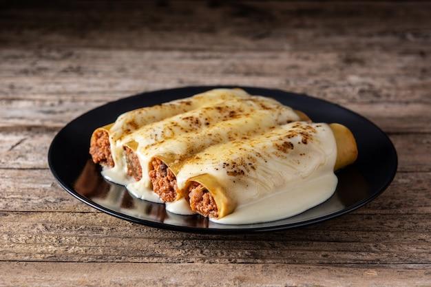 Heerlijke vlees cannelloni pasta op houten tafel