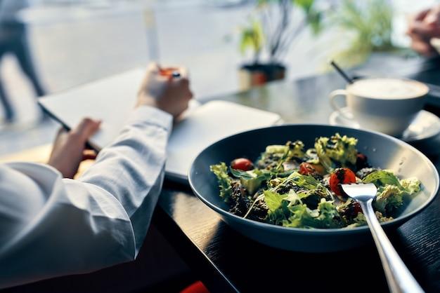 Heerlijke voedselsalade in een kladblok van de plaatvork met de inscriptie en de vrouw in het interieur van de shirtkoffie