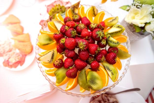 Heerlijke vruchten in plaat op een feestelijke tafel.
