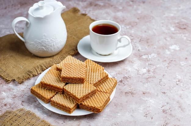 Heerlijke wafels en een kopje koffie voor het ontbijt op lichte achtergrond, bovenaanzicht