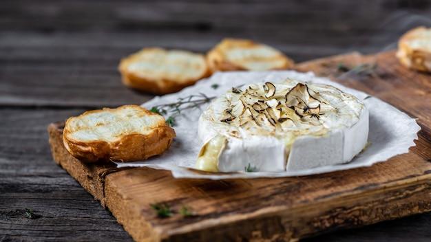 Heerlijke warme gebakken camembert met tijm en stokbrood op houten tafel.