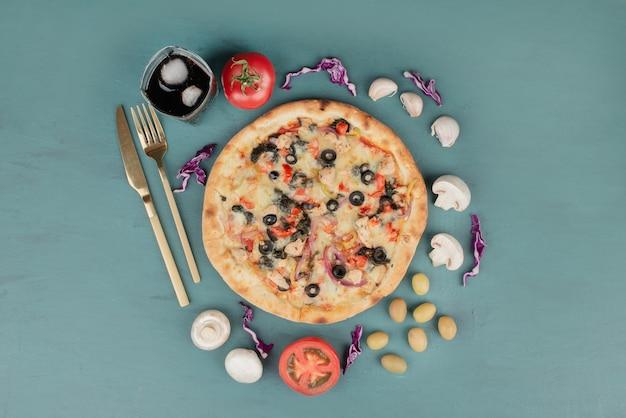 Heerlijke warme pizza met olijven, champignons en tomaten op blauwe ondergrond.
