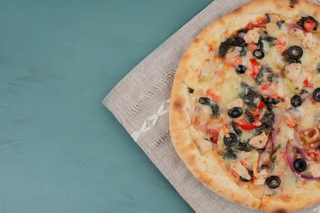 Heerlijke warme pizza met olijven en tomaten op blauwe tafel.