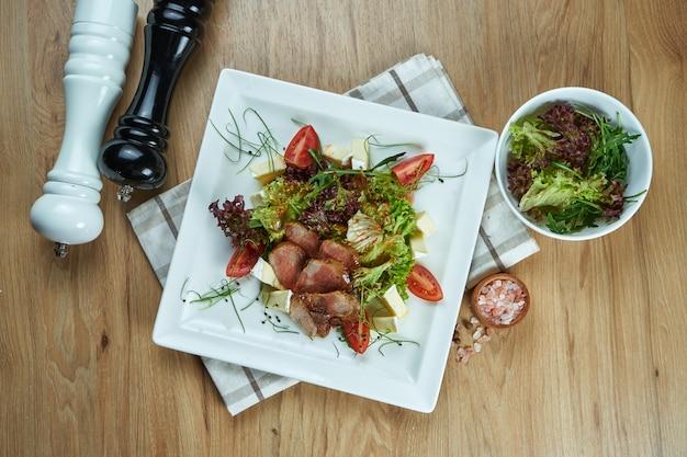 Heerlijke warme salade met eendenborst, tomaten, brie, sla en zoete saus. dieet en gezonde salade. smakelijke voedselfotografie