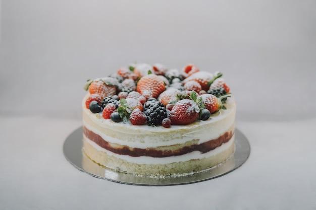 Heerlijke witte cake met natuurlijk fruit en wit poeder bovenop op witte achtergrond