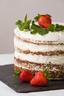 Heerlijke witte slagroomtaart met aardbei op het zwarte bord naakte cake met slagroom en bessen